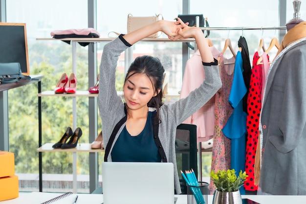 Belle femme occasionnelle asiatique fatiguée pendant le démarrage d'une petite entreprise entrepreneur pme dans un magasin de vêtements. Photo Premium