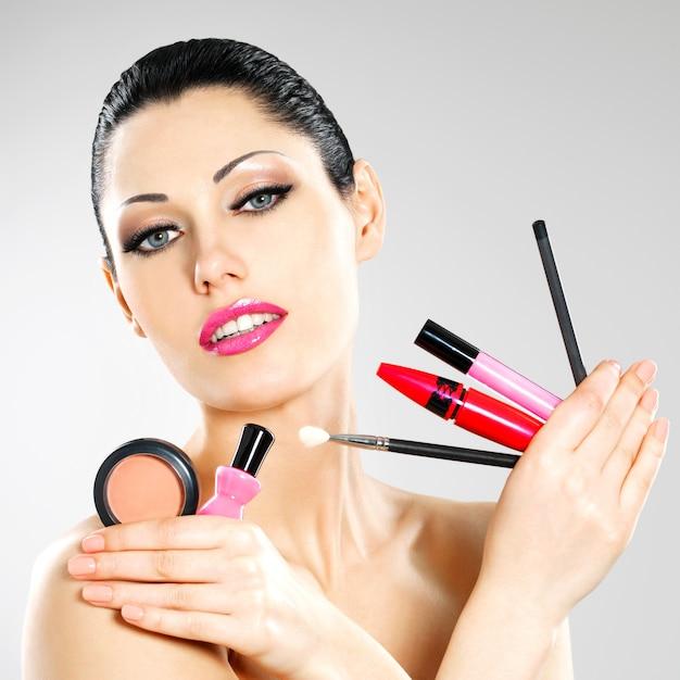Belle Femme Avec Des Outils Cosmétiques De Maquillage Près De Son Visage. Photo gratuit