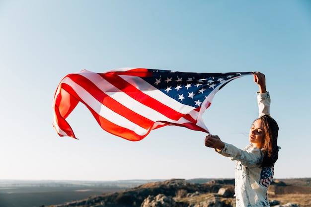 Belle femme patriotique avec des drapeaux américains flottant Photo gratuit