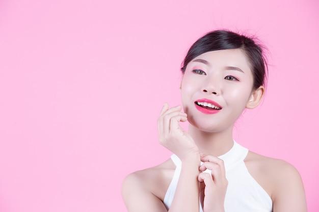 Belle femme avec une peau saine et beauté sur un fond rose. Photo gratuit