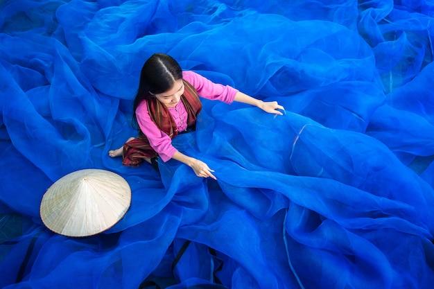 Belle femme pêcheur répare des filets de pêche, pêcheur nettoie la pêche thaïlandaise Photo Premium