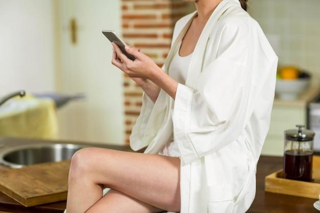 Belle femme en peignoir assis sur le plan de travail et en tapant un sms dans la cuisine Photo Premium