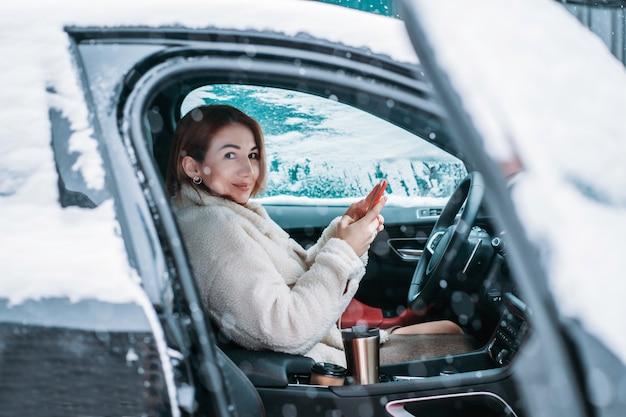 Belle femme pilote nsitting au volant de sa voiture Photo gratuit