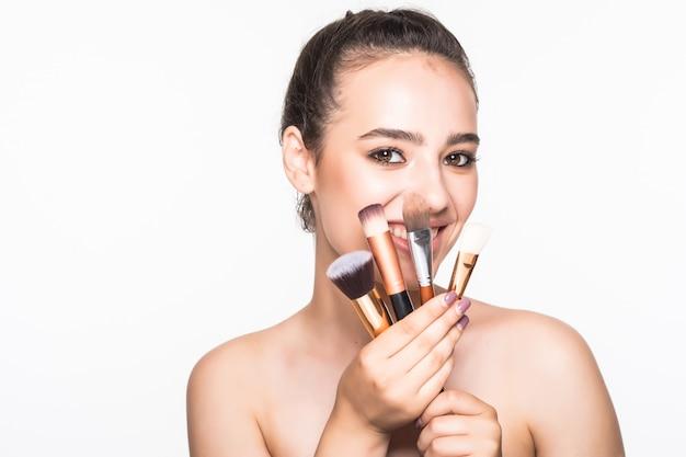 Belle Femme Avec Des Pinceaux De Maquillage Près De Son Visage Isolé Sur Mur Blanc Photo gratuit