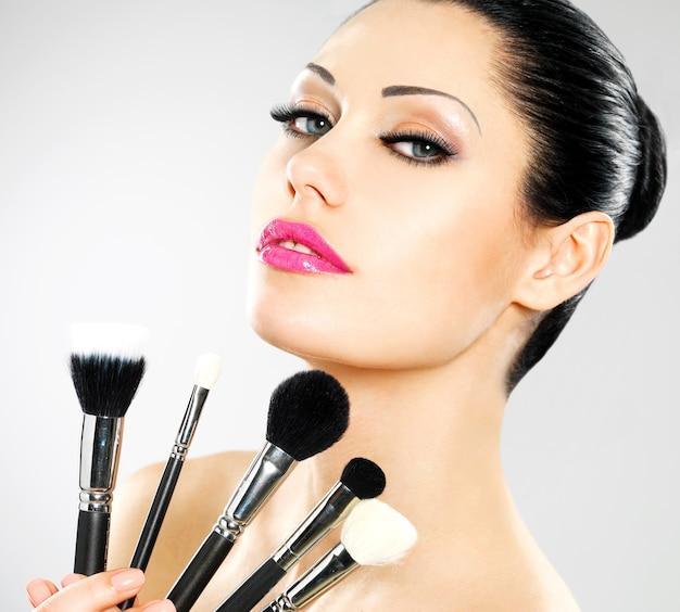 Belle Femme Avec Des Pinceaux De Maquillage Près De Son Visage. Jolie Fille Pose Avec Des Outils Cosmétiques Photo gratuit