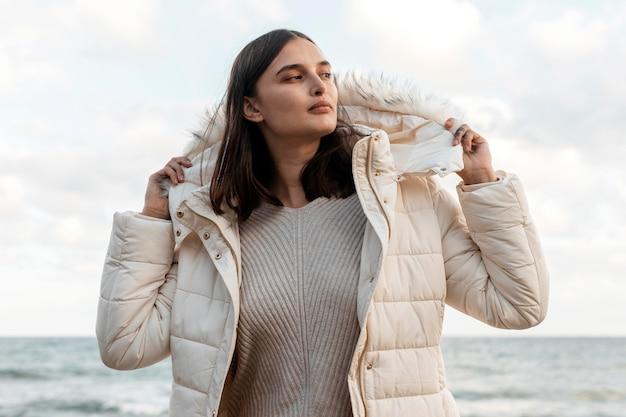 Belle Femme à La Plage Avec Veste D'hiver Photo gratuit