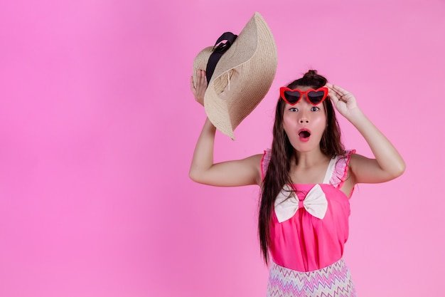 Une belle femme portant des lunettes rouges avec un grand chapeau sur un rose. Photo gratuit