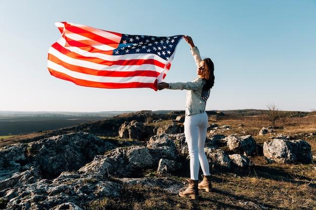 Belle femme posant avec un drapeau américain au sommet de la montagne Photo gratuit