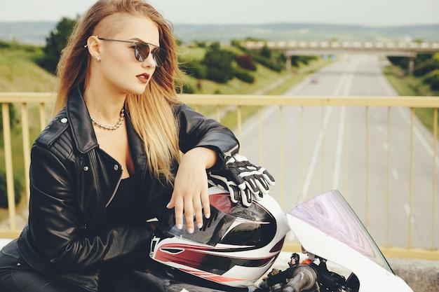 Belle Femme Posant Avec Des Lunettes De Soleil Sur Une Moto Photo gratuit