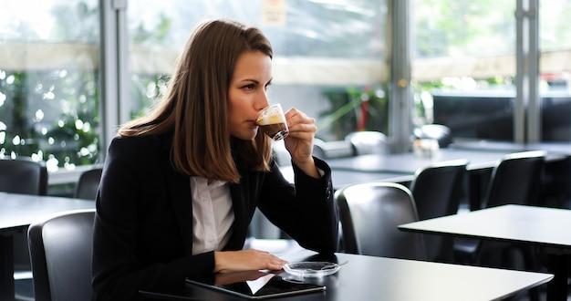 Belle femme prenant un café dans un café Photo Premium