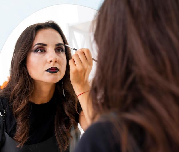 Belle femme prépare le maquillage pour halloween Photo gratuit