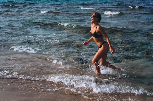 Belle femme qui court au bord de l'océan Photo gratuit