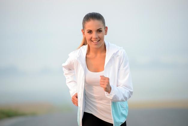 Belle femme qui court dans un parc verdoyant en été ensoleillé. Photo Premium