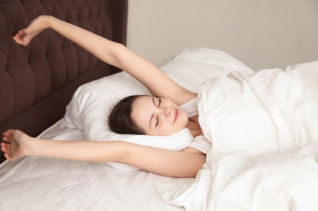 Belle femme qui s'étend avec plaisir au lit Photo gratuit