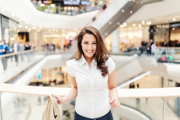 Belle Femme De Race Blanche Avec Un Sourire à Pleines Dents Habillé Décontracté Posant Dans Un Centre Commercial. Photo Premium
