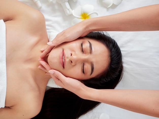 Belle femme recevant un massage facial dans le spa. Photo Premium