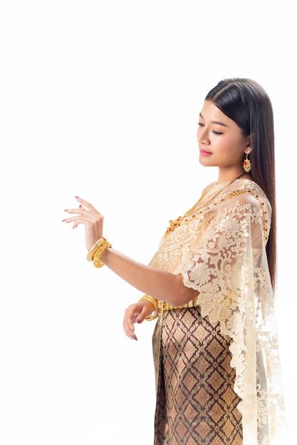 Belle femme regarde sa main en costume traditionnel national de la thaïlande. isotate Photo Premium