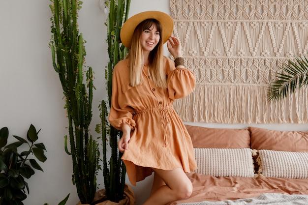 Belle Femme En Robe De Lin Et Chapeau De Paille Posant Dans Un Appartement De Style Bohème Photo gratuit