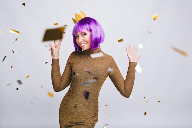 Belle Femme En Robe De Luxe S'amusant à Voler Des Guirlandes. Elle Porte Une Coupe De Cheveux Violette, Une Couronne En Or, Souriant Photo gratuit
