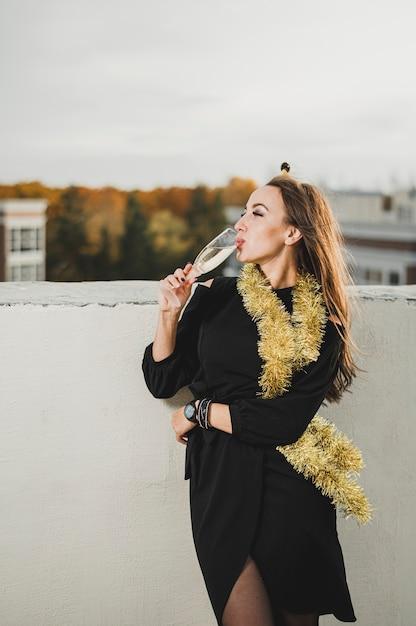 Belle femme en robe noire buvant du champagne Photo gratuit