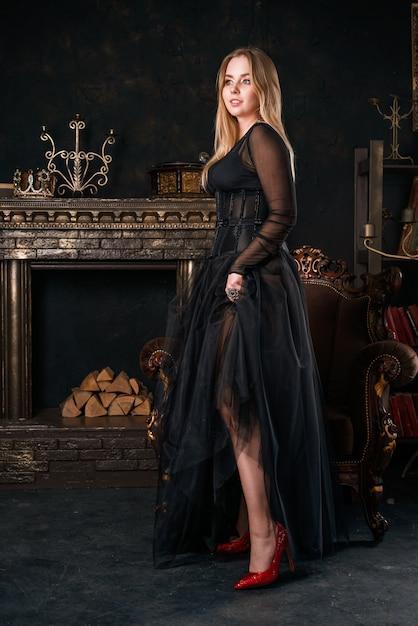 Belle femme en robe noire avec corset se dresse dans des chaussures rouges Photo Premium