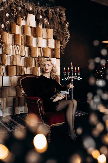 Belle femme en robe noire s'assoit devant un mur de livres et un décor de noël Photo gratuit