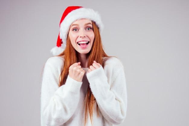 Belle Femme Rousse Au Gingembre Portant Chandail Tricoté Blanc Et Chapeau De Père Noël Croix Doigt Faire Des Souhaits Photo Premium