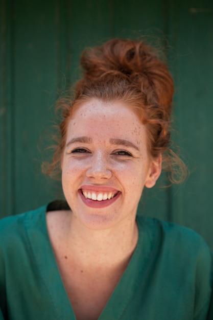 Belle femme rousse souriante regardant la caméra Photo gratuit