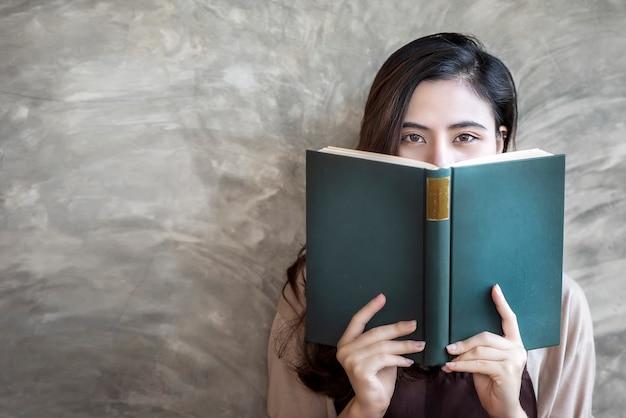 Belle femme se cache le visage derrière un livre vert tout en regardant la caméra. Photo Premium