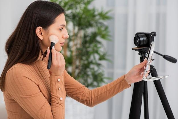 Belle Femme Se Maquillant à La Caméra Photo gratuit