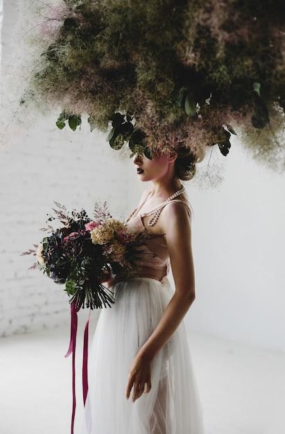 Belle femme se tient avec un bouquet parmi le linge suspendu dans la chambre Photo gratuit