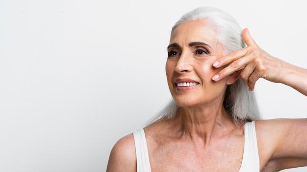 Belle femme senior appliquant un traitement Photo gratuit