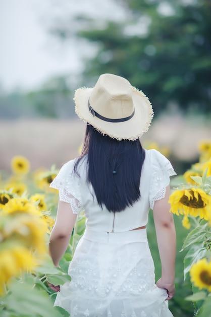 Belle femme sexy dans une robe blanche marchant sur un champ de tournesols Photo gratuit