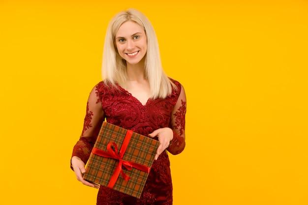 Une Belle Femme Sexy Dans Une Robe Rouge Tenir Dans Les Mains Des Cadeaux Sur Fond Jaune Photo Premium
