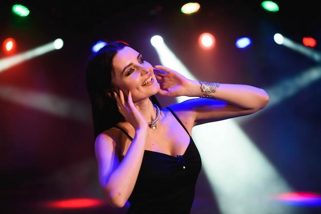 Belle femme sexy sur fond de lampes colorées. Photo Premium