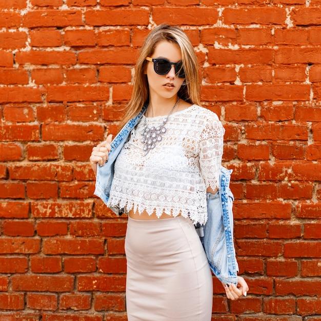Belle Femme Sexy Jeune Hipster Dans Un Chemisier En Dentelle Blanche Et Une Veste En Jean à Lunettes De Soleil Noires Dans Une Jupe Beige Pose Près D'un Mur De Briques Rouges Photo Premium