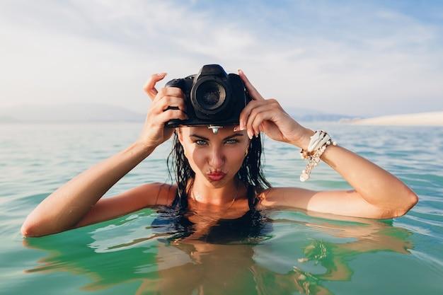 Belle Femme Sexy, Peau Bronzée, Maillot De Bain Bikini Noir, Debout Dans L'eau Bleue, Tenant Un Appareil Photo Numérique, Vacances D'été Chaudes Et Tropicales, Tendance De La Mode, Séduisant, Humide Photo gratuit