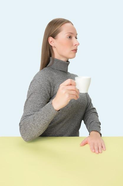 Belle Femme Solitaire Assise Et à La Triste Tenant La Tasse De Café à La Main. Closeup Portrait Tonique Dans Un Style Minimalisme Photo gratuit