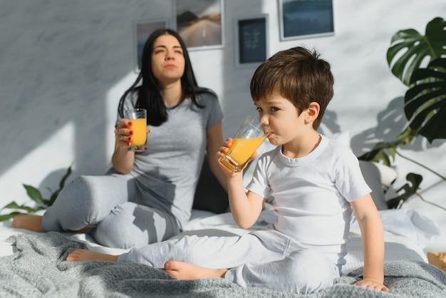 Belle Femme Avec Son Fils, Boire Du Jus Le Matin Au Lit Photo Premium