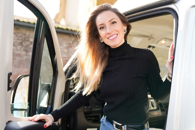 Belle Femme Souriante Au Volant De Camping-car Van Home Van Dans Le Concept De Style Vanlife Photo Premium