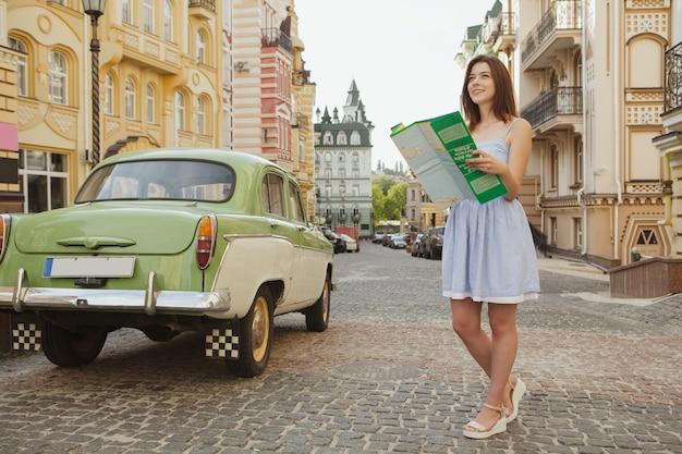 Belle femme souriante, cherche une place sur la carte, debout dans la rue Photo Premium