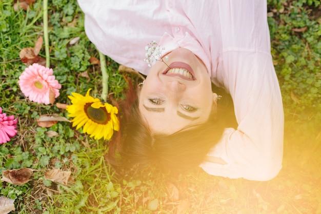 Belle femme souriante et couchée sur l'herbe Photo gratuit