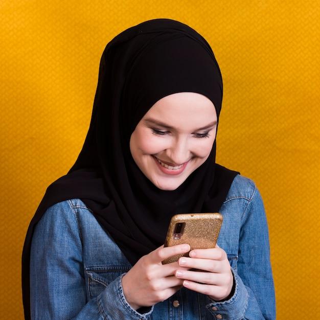 Belle femme souriante, lisant des messages sur smartphone sur fond jaune Photo gratuit