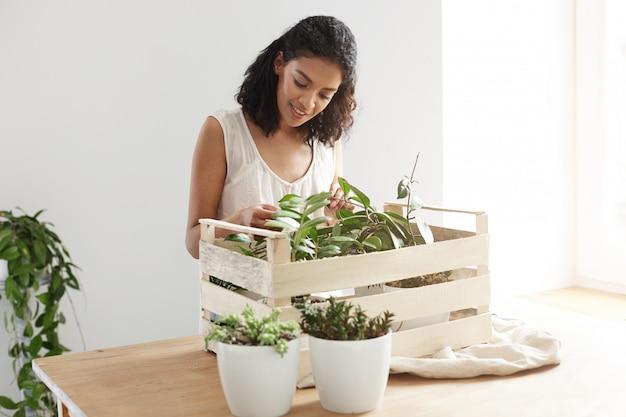 Belle Femme Souriante En Prenant Soin Des Plantes En Boîte Au Lieu De Travail Photo gratuit