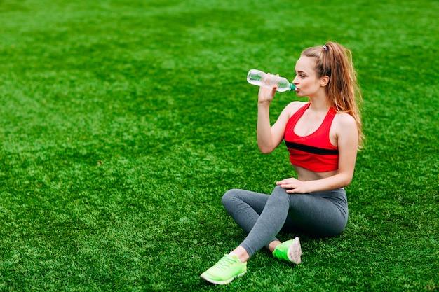 Belle femme souriante se détendre sur l'herbe dans le parc pendant l'entraînement. concept sport et fitness Photo Premium