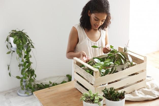 Belle Femme Souriante Travaillant Avec Des Plantes En Boîte Au Lieu De Travail Mur Blanc. Photo gratuit