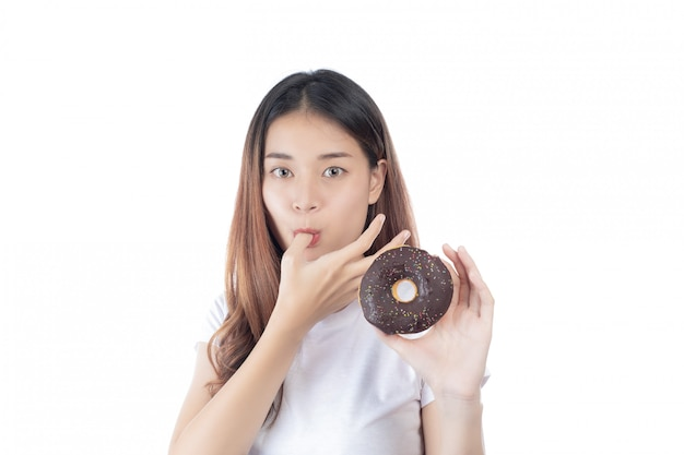 Belle femme avec un sourire heureux, tenant un beignet à la main, isolé sur fond blanc. Photo gratuit
