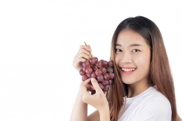 Belle femme avec un sourire heureux, tenant un raisin de la main, isolé sur fond blanc. Photo gratuit