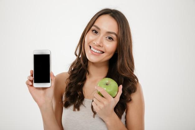 Belle Femme Avec Un Sourire Parfait Démontrant Un Téléphone Mobile Argenté Sur L'appareil Photo Et La Tenue, Pomme Verte Isolée Sur Mur Blanc Photo gratuit