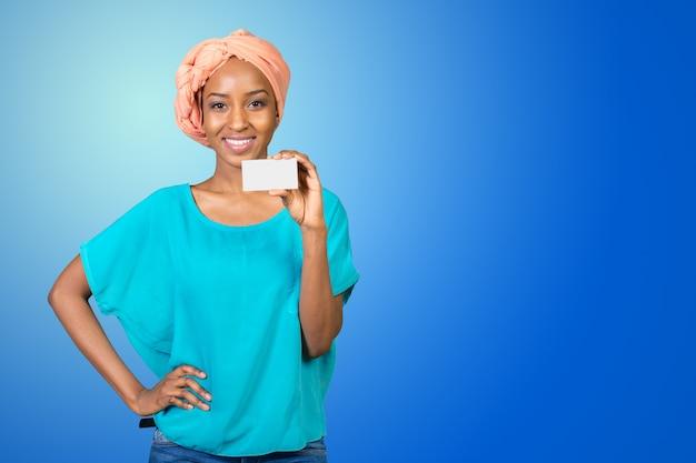 Une belle femme avec un sourire parfait est titulaire d'une carte de visite Photo Premium